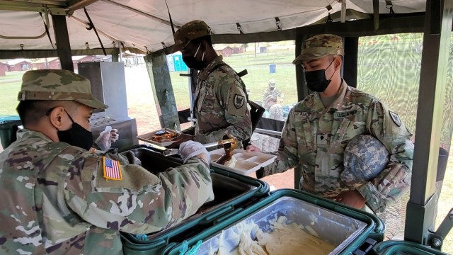 Culinary Specialists assigned to Headquarters and Headquarters Company, 311th Signal Command (Theater) serve a welcome hot meal to fellow Army Reserve Soldiers in and beside their Mobile Kitchen Trailer during range qualification operations at Schofield Barracks, Apr. 9, 2021.