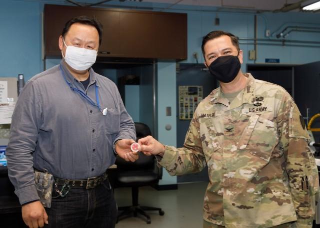 "Col. Thomas Matelski, right, commander of U.S. Army Garrison Japan, presents Tohru Yamaguchi, a window clerk at the Camp Zama U.S. Post Office, with a commander's ""poker chip"" at the facility on Camp Zama, Japan, May 14."