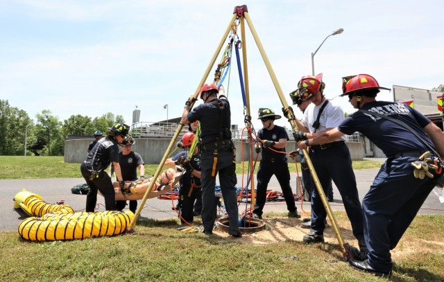 """Once the """"victim"""" was successfully extracted, the two rescue workers remove their masks and breathe fresh air again as ambulance workers completed their portion of the simulated rescue."""