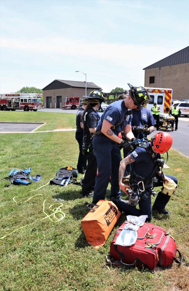 """02: Two Fort Knox firefighters work together within an open manhole to extract the """"victim,"""" while others remain above ground to operate the rescue equipment."""