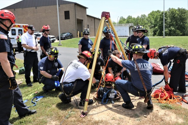 """Two Fort Knox firefighters work together within an open manhole to extract the """"victim,"""" while others remain above ground to operate the rescue equipment."""