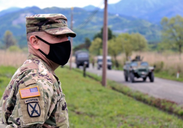 Col. Thomas J. Verell, Jr., Japan Engineer District commander, takes in a JGSDF convoy as the JGSDF members practice counter IED measures at Kita Fuji, May 15. The exercise is designed to help Central Readiness Regiment engineers prepare for possible deployment abroad in support of peace keeping missions.