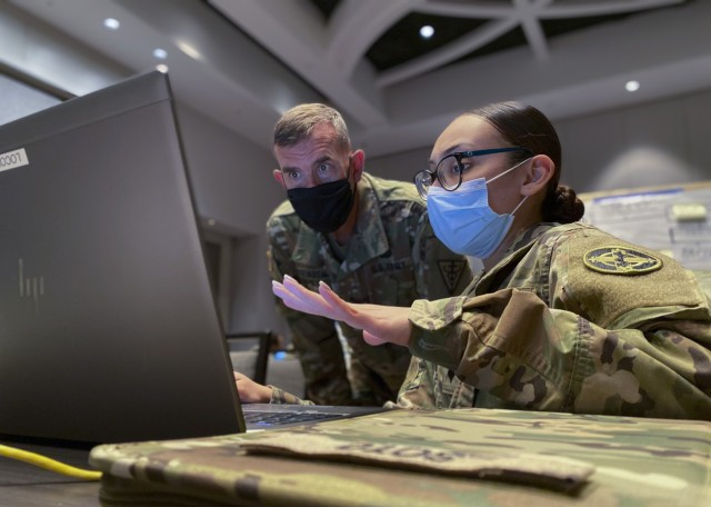 U.S. Army Reserve Spc. Kimberly Soto (right), a human resources specialist with the 338th Medical Brigade, 3rd Medical Command Deployment Support, goes over her personal readiness processes with Commanding General Maj. Gen. Joe Robinson, 3rd Medical Command Deployment Support, during U.S. Army North's exercise Vibrant Response 21. This year's exercise virtually trained and certified Task Force 76 and its headquarters elements through a command post exercise, based on a simulated chemical, biological, radiological and nuclear incident. (U.S. Army Photo by Bethany L. Huff)