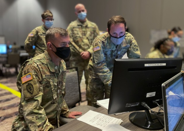 U.S. Army Reserve Spc. Kevin Maldonado (right), a signal support specialist with the 338th Medical Brigade, 3rd Medical Command Deployment Support, demonstrates his simulation operation role to Commanding General Maj. Gen. Joe Robinson, 3rd Medical Command Deployment Support, during U.S. Army North's exercise Vibrant Response 21. This year's exercise virtually trained and certified Task Force 76 and its headquarters elements through a command post exercise, based on a simulated chemical, biological, radiological and nuclear incident. (U.S. Army Photo by Bethany L. Huff)