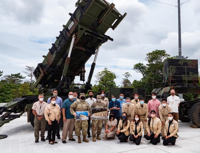 Col. Thomas J. Verell, Japan District, U.S. Army Corps of Engineers commander; Lt. Col. Rosanna Clemente, 1st Battalion, 1st Air Defense Artillery Regiment commander; employees of the Japan District, U.S. Army Corps of Engineers, and contractors from the Nishimatsu Construction Company gather in front of a Patriot missile launching station. The 1st Battalion, 1st Air Defense Artillery Regiment celebrated the unveiling of the first Patriot Missile Storage Facility in Japan during a ribbon cutting ceremony at Kadena Air Base, Japan May 19.