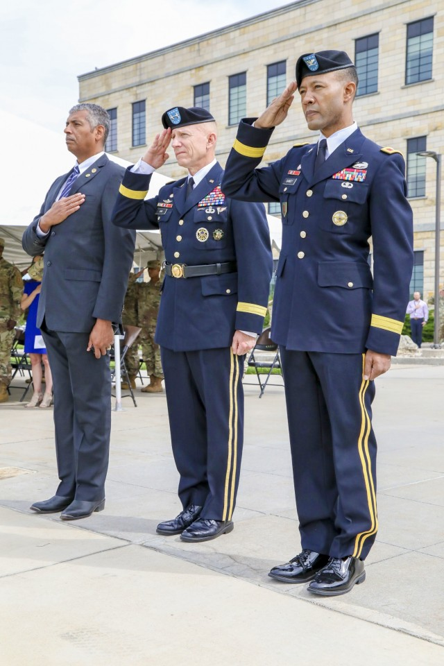 Left to Right: U.S. Army Gen. (Ret.) Vincent Brooks, U.S. Army Maj. Gen. Douglas A. Sims, the Fort Riley and 1st Infantry Division commanding general, and U.S. Army Brig. Gen. Andrew Gainey, the deputy commanding general of maneuver, 1st Infantry Division, pay their respects during the National Anthem at a ceremony at the Fort Riley and 1st Infantry Division Headquarters building at Fort Riley, Kansas, May 24, 2021. The ceremony was held to promote Gainey from the rank of colonel to brigadier general. (U.S. Army photo by Spc. Alvin Conley, 19th Public Affairs Detachment)