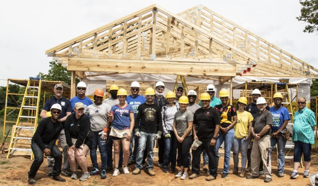 U.S. Army Reserve Soldiers assigned to the Mobilization Demobilization Operations Center (MDOC) from the 2-381st Training Support Battalion, 120th Infantry Brigade, First Army Division West, along with other volunteers, stand together for a group photo after completing the roof framing on a house construction site during a Habitat for Humanity housing project in Waco, Texas, May 16.  The participants from the MDOC team used this volunteering opportunity to frame a creative way for team and leadership building while also supporting the local community. (Courtesy Photo)