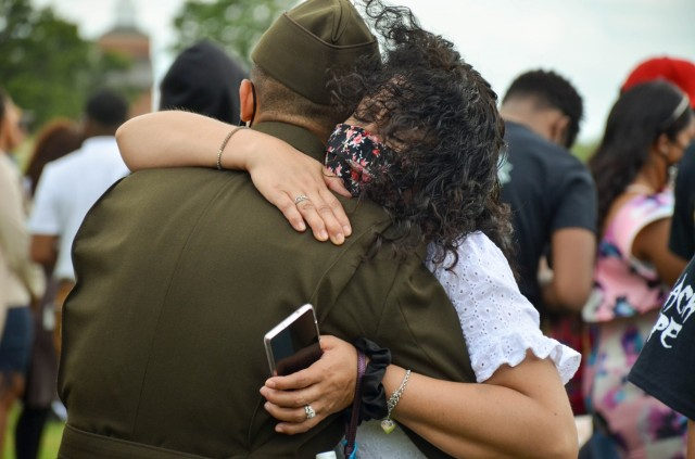 Pvt. Christian Jimenez gets a hug from his mother, Yesnia Soloria, after graduating from One Station Unit Training with Company B, 795th Military Police Battalion, May 20 on Gammon Field. Family and friends are once again being invited to attend graduations in person after more than a year of virtual ceremonies due to COVID-19 mitigation efforts.