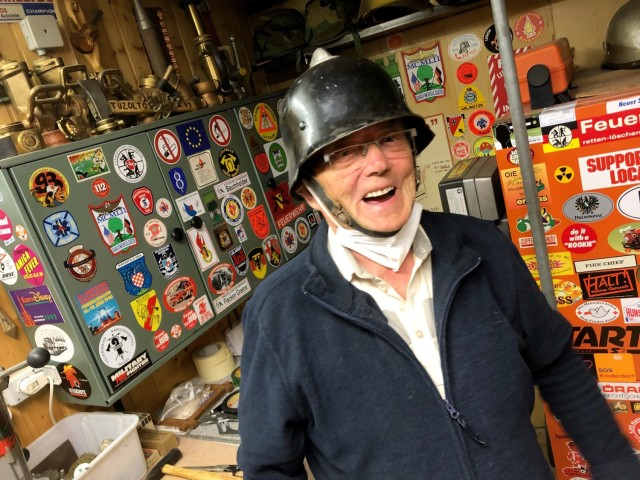 92-year-old Horst Teumer laughs as he shows off the original firefighting helmet he wore when he joined the Baumholder Military Community Fire Department in 1954. Teumer eventually became the Fire Chief on the Baumholder installation and retired in 1994.