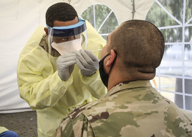 A combat medic at Wiesbaden Army Health Clinic, swabs a patient for COVID-19 testing, June 12.