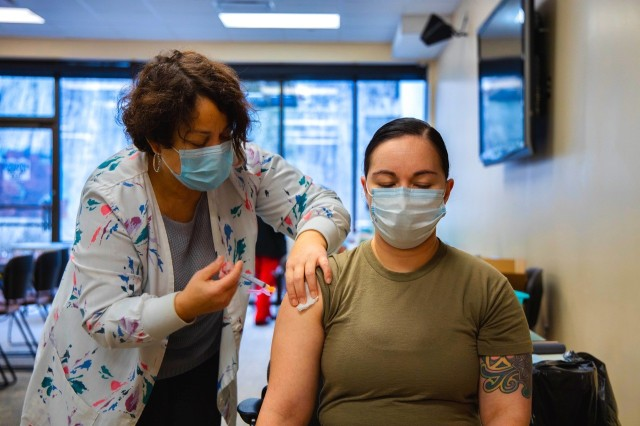 Maj. Elizabeth Patricola, from Fox Army Health Center, receives her first dose of the COVID-19 vaccine administered by Tamiris Centeno, a public health nurse at Fox.
