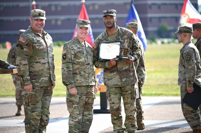 Spc. Jaleel Hunn, a 92A automated logistics specialist and winner of the Combined Arms Support Command's Best Warrior of the Year title, is acknowledged by Maj. Gen. Rodney D. Fogg, CASCOM and Fort Lee commanding general, and Command Sgt. Maj. Jorge C. Escobedo, CASCOM CSM, during an award ceremony today on Fort Lee's Seay Field. Hunn is a native of Inglewood Calif. (U.S. Army photo by Tom Burcham)