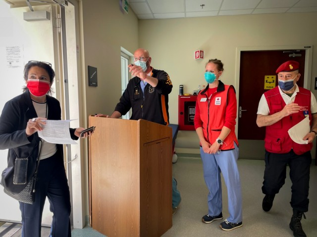 Volunteers from the Vicenza chapter of the Italian Relief Corps of the Order of Malta, American Red Cross, and staff members of the USAHC-Vicenza check-in and direct a host nation professional to receive the first dose of the Pfizer vaccine May 25, 2021.