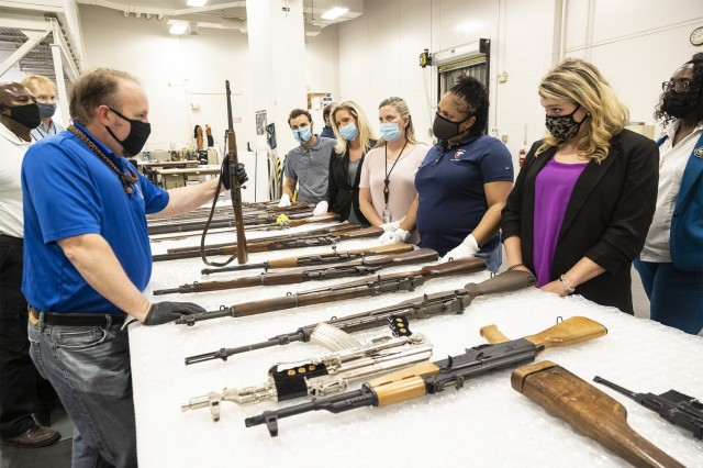 Team members from the Army Materiel Command's Public Affairs and Protocol offices watch as an employee from the Museum Support Center displays weapons from the Civil War, World II and other time periods.