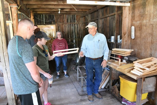 Rolly Churchill talks about the different types of hive frames that serve as the structure for bees to build the honeycomb. Veterans and active-duty service members toured the bee farm and workshop at Churchill Farms in Watertown on May 24, and they received hands-on instruction in beekeeping. The tour was made possible through Cornell Cooperative Extension of Jefferson County and the Farm OPS program. (Photo by Mike Strasser, Fort Drum Garrison Public Affairs)