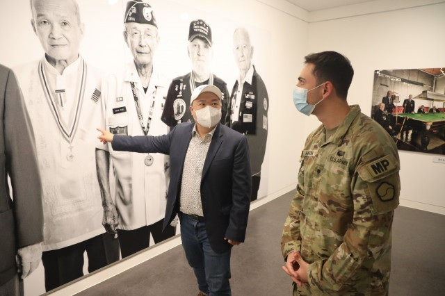 Photographer Ramy Hyun explains his exhibit Project Soldier to Spc. Scott Anderson, 188th Military Police Company, 94th Military Police Battalion, at the United Nations Peace Memorial in Busan. Soldiers from 19th Expeditionary Sustainment Command visited the memorial as part of a spiritual resilience training event organized by the 19th ESC Chaplain's Office.