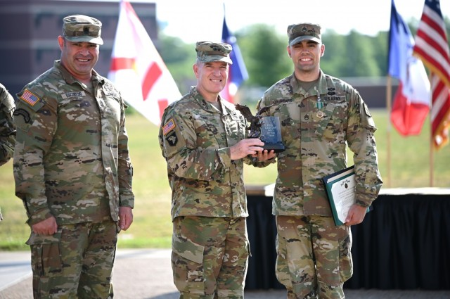 Staff Sgt. Ryan Columbare, a 42R musician and winner of the Combined Arms Support Command's Noncommissioned Officer of the Year title, is congratulated by Maj. Gen. Rodney D. Fogg, CASCOM and Fort Lee commanding general, and Command Sgt. Maj. Jorge C. Escobedo, CASCOM CSM, during an award ceremony today on Fort Lee's Seay Field. Columbare holds a master's degree in music specializing in the trumpet. (U.S. Army photo by Tom Burcham)