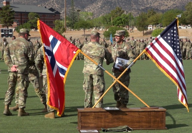 Leaders from Co. C, 309th Military Intelligence Battalion, U.S. Army Intelligence Center of Excellence honor Soldiers who earned the Norwegian Foot March Badge at Fort Huachuca, Ariz.