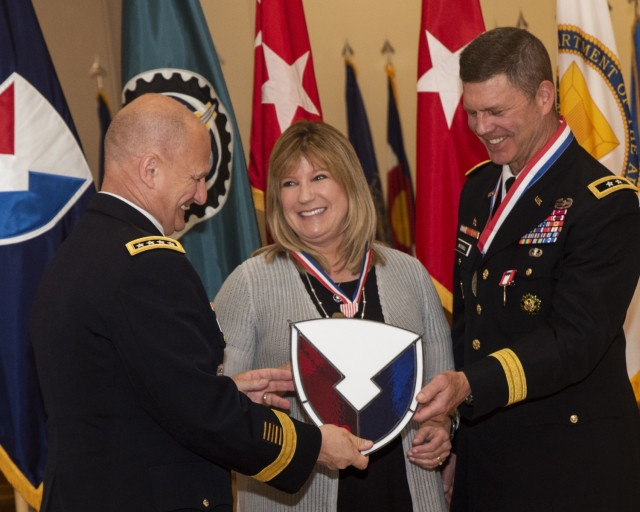 Gen. Ed Daly presents a stained glass AMC logo to Maj. Gen. Daniel Mitchell and his wife, Lori, during a relinquishment of command and retirement ceremony May 27. (Photo by Linda Lambiotte, ASC Public Affairs)