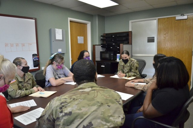 Staff Sergeant Jeannine Valencia, noncommissioned officer in charge, Patient Administration Division, Blanchfield Army Community Hospital, center, meets with a group of Soldiers and civilian employees May 21. Valencia was recently inducted into the Sgt. Audie Murphy Club for her leadership skills and commitment to Soldiers and Families.