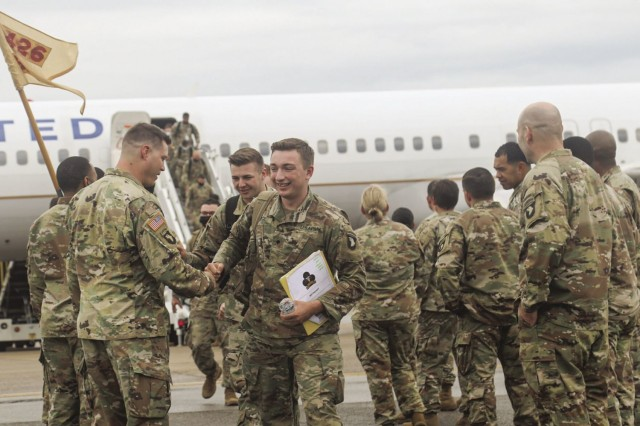 Specialist John Michael Rice, a combat medic specialist assigned to 1st Battalion, 32nd Cavalry Regiment, 1st Brigade Combat Team, 101st Airborne Division (Air Assault), shakes hands with Chap. (Capt.) Matthew Shaw, 1-32nd Cav. Regt., as he walks away from the plane that brought him and more than 200 other Bastogne Soldiers home from their 12-week deployment to Chicago, Illinois.