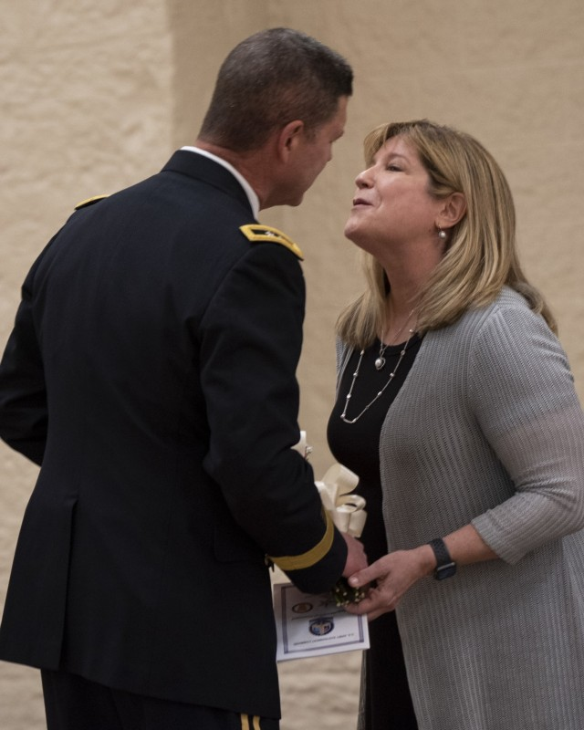 Maj. Gen. Daniel Mitchell kisses his wife, Lori, after presenting her with flowers during his retirement ceremony May 27 Mitchell also relinquished command of the U.S. Army Sustainment Command during the ceremony. (Photo by Linda Lambiotte, ASC Public Affairs)