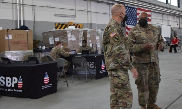 WIESBADEN, Germany – Staff Sgt. Nkruma Alladin explains to Brig. Gen. Jed Schaertl how the blood donor stations are set up and what the Army Reserve Soldiers are doing at each station.