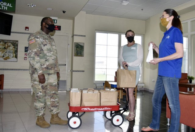 VICENZA, Italy - Sgt. Deron Thompson, behavioral health at the U.S. Army Health Center, Vicenza, receives some 'Resiliency through Art' individual kits May 5, 2021, by Michelle Sterkowicz, U.S. Army Garrison Italy Art Center program manager, (right) and Aurora Venden, American Red Cross Interim Regional program manager. The Art Center worked in partnership with volunteers and organizations to deliver approximately 700 kits to help discover the benefits of art during COVID-19.