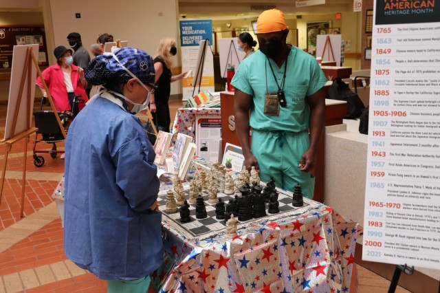 U.S. Air Force Capt. Suji Yoon, Brooke Army Medical Center perioperative nurse, left, and U.S. Air Force Capt. Kenneth Ashianor, BAMC perioperative nurse, engage in a friendly game of chess during the Asian American and Pacific Islander Observance in the medical mall, May 27, 2021. (U.S. Army photo by Robert A. Whetstone)