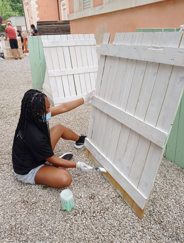 VICENZA, Italy: Better Opportunity for Single Soldiers volunteer Sgt. Jonel Knight repaints a fence at the kindergarten school in Quinto Vicentino May 22, 2021. She arrived here a couple months ago and she has already contributed her time within the community. Approximately 20 volunteers from BOSS, Vicenza Sergeant Morales Club and other Vicenza military community members participated in the project.