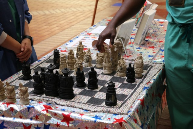 U.S. Air Force Capt. Suji Yoon, Brooke Army Medical Center perioperative nurse, left, and Capt. Kenneth Ashianor, BAMC perioperative nurse, engage in a friendly game of chess during the Asian American and Pacific Islander Observance in the medical mall May 27, 2021. (U.S. Army photo by Robert A. Whetstone)