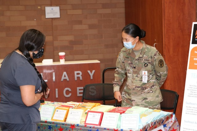 U.S. Army Spc. Doyeon Park, Brooke Army Medical Center operation room specialist, explains the different types of tea by country that is available for patients and staff to sample during the Asian American and Pacific Islander Observance in the medical mall, May 27, 2021. (U.S. Army photo by Robert A. Whetstone)