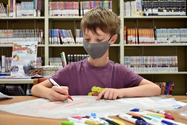 "Ricky Chapman, 8, makes a kite during a ""Fun Friday"" event at the Sagamihara Family Housing Area Library, SFHA, Japan, May 28."