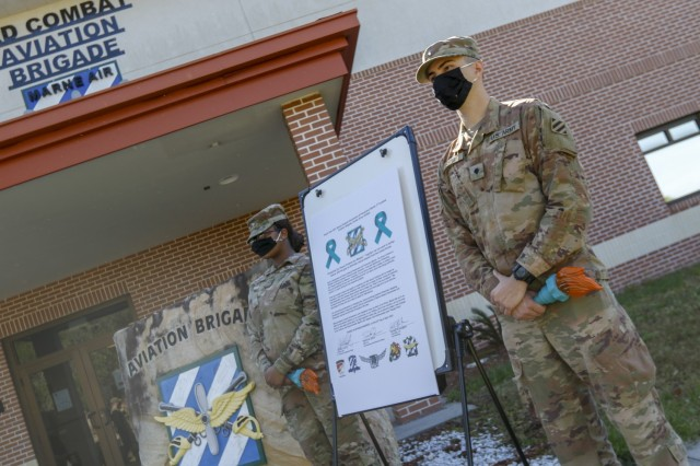 """Representatives of the Marne Air Advisory Board, Pvt. Kelle Ross (left) and Spc. Cameron Forte (right), assigned to the the 3rd Combat Aviation Brigade, 3rd infantry Division, stand next to the sexual assault awareness and prevention proclamation, Apr. 27 at Hunter Army Airfield, Georgia. The theme, """"protecting our people protects our mission,"""" emphasizes how every service member, regardless of rank, can encourage behaviors that foster a climate of dignity and respect, and in doing so, help ensure readiness to complete the mission."""