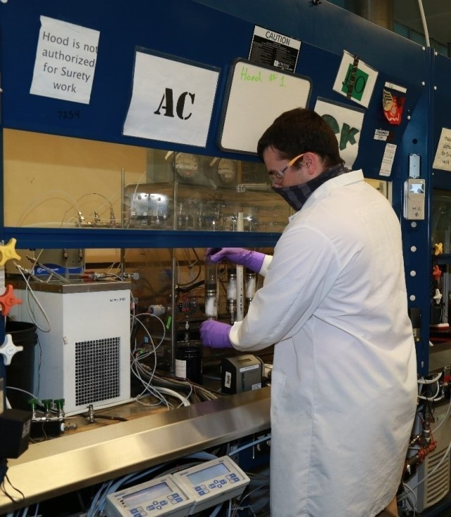 Aaron Salgado, a DEVCOM CBC chemist, places a tube containing a layer of carbon from the second source into a testing system that will analyze the time it would take a chemical agent to break through it.