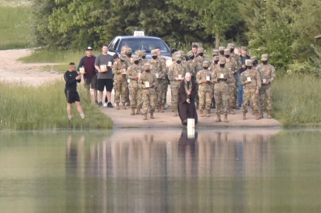 Chaplain (Capt.) Christopher Mohr, 58th Transportation Battalion chaplain, leads a lantern floating event Sunday evening at Bloodland Lake.
