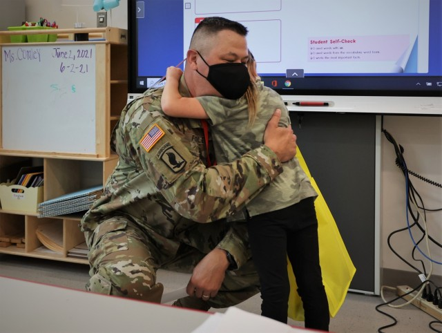Kingsolver first-grader Avery Brown hugs Garrison Command Sgt. Maj. William Fogle, who presented her with several coins in front of her class June 3 in recognition for her efforts raising funds for the 2021 Army Emergency Relief campaign.