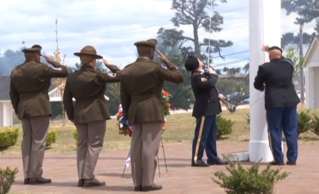 Post Command Sgt. Maj. Philson Tavernier, Staff Sgt. Josiah Bartz and Brig. Gen. Milford H. 'Beags' Beagle Jr, Fort Jackson commander salute as the flag is lowered during the Memorial Day ceremony at Centennial Park May 31. (Screenshot)