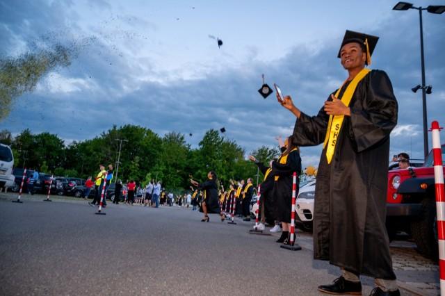 Stuttgart High School graduates toss their graduation caps during an outdoor, drive-in graduation ceremony at Panzer Barracks, Germany, June 2, 2021.