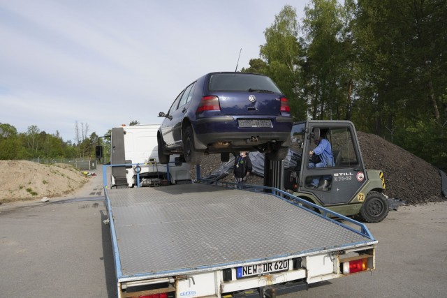 A forklift raises a vehicle onto an FMWR tow truck from the abandoned vehicle lot to a location to be salvaged and sold as an initiative to rid the installation of abandoned vehicles.