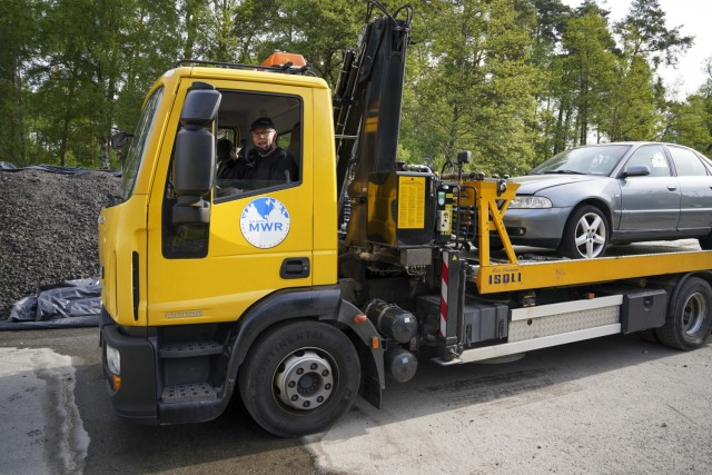 An FMWR tow truck tows abandoned vehicles to a location to be salvaged and sold as an initiative to remove abandoned vehicles from the installation.