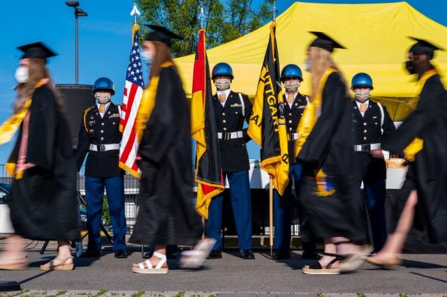Stuttgart High School graduates walk toward the graduation stage during an outdoor, drive-in graduation ceremony at Panzer Barracks, Germany, June 2, 2021.