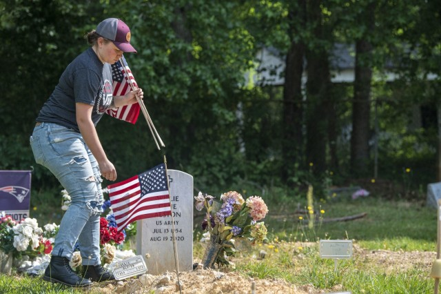 First Lt. Jessica Hindman, officer in charge of the Memorial Day Ride event, places flags at the Gates of Heaven Cemetery in Columbia May 28.