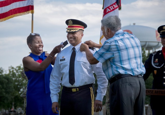 Brig. Gen. Richard Harrison enjoys his new shoulder boards his wife, Tyra, and father, Roger, apply to his uniform shirt. Harrison was promoted to brigadier general June 2, 2021, at the Old Post Quadrangle on Fort Sill, Oklahoma.