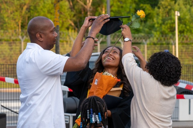 A Stuttgart High School graduate has fun while taking photos during an outdoor, drive-in graduation ceremony at Panzer Barracks, Germany, June 2, 2021.