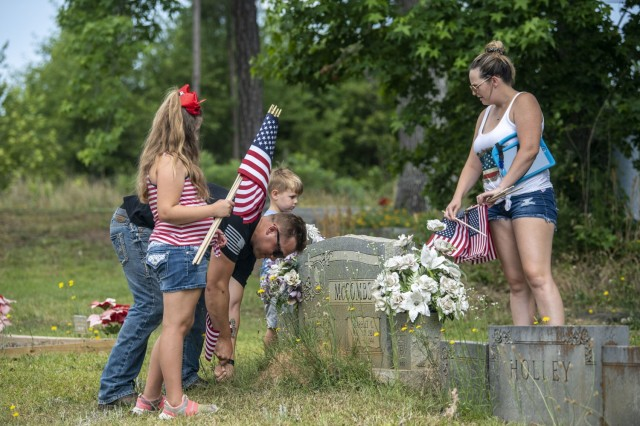 A Soldier and his family place flags at the Gates of Heaven Cemetery in Columbia during the 165th Infantry Brigade Memorial Day Ride event May 28.