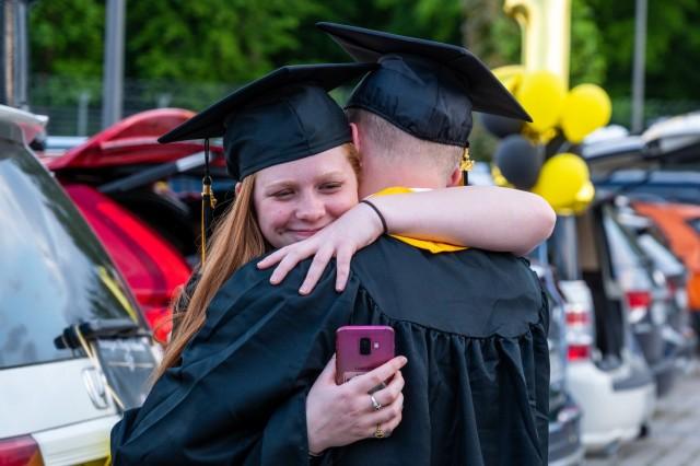 Two Stuttgart High School graduates hug during an outdoor, drive-in graduation ceremony at Panzer Barracks, Germany, June 2, 2021.