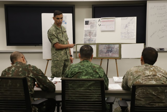Uruguayan Army Captain Jorge Amil Andrés presents his Battle Forge OPORD to three WHINSEC evaluators as part of the culmination exercise of the Company phase. This phase is one of three main phases of the WHINSEC Captain's Career Course – Maneuver. U.S. Army Photo by Sr. Daniel Cruz.
