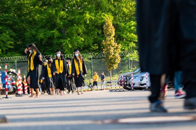 Stuttgart High School graduates walk between an audience of cars during an outdoor, drive-in graduation ceremony at Panzer Barracks, Germany, June 2, 2021.