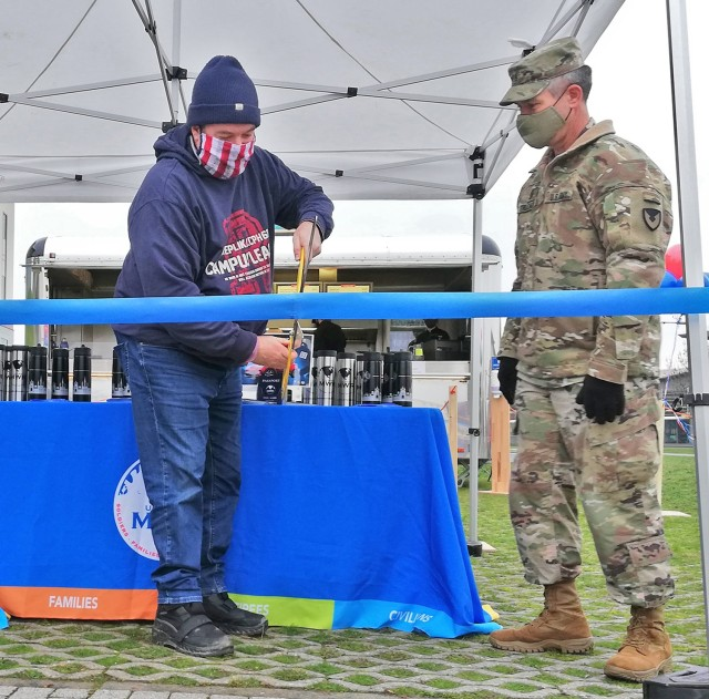 Photo by Karl Weisel U.S. Army Garrison Command Sgt. Maj. Christopher Truchon (right) look on as Wiesbaden Entertainment Center Manager Bill Montgomery cuts the ribbon to mark the opening of the new Silver Spoon's Burger Bliss on Clay Kaserne Jan. 7, 2021.